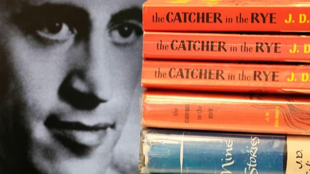 Ein schwarz-weiss Porträt von Salinger. Neben dem Porträt ist ein Stapel mit Büchern von ihm.