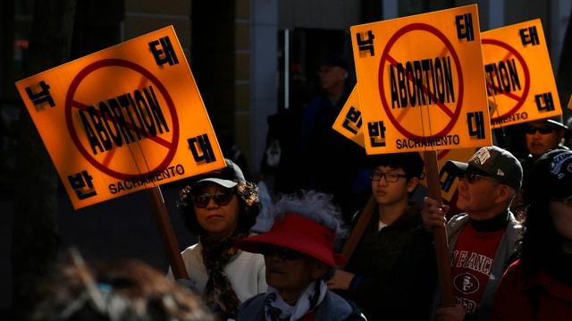 Demonstranten mit Anti-Abtreibungs-Schildern.