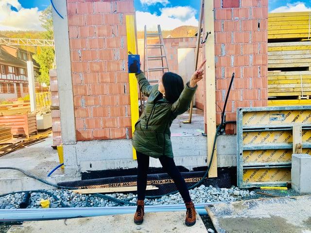 Annette König hält den Roman «Primitivo» von Pedro Lenz in der Hand und steht auf einer Baustelle
