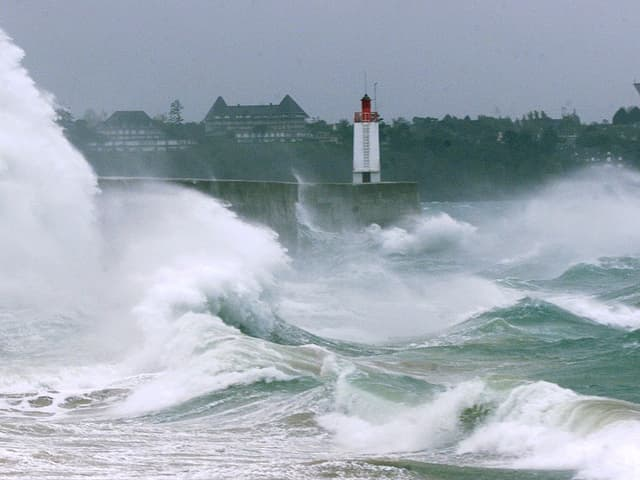 Am Strand jagt eine Welle die nächste und meterhohe Fontänen spritzen an der Hafenmolle in die Höhe.