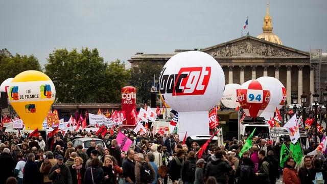 Menschen, Ballone im Hintergrund steht die Französische Nationalversammlung