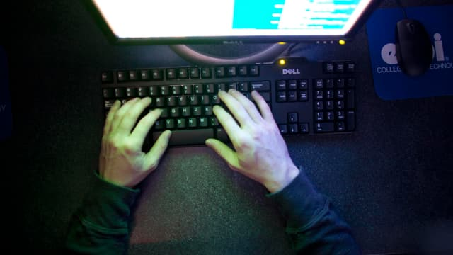 Hände eines Mannes auf einer Computertastatur vor einem Computerbildschirm