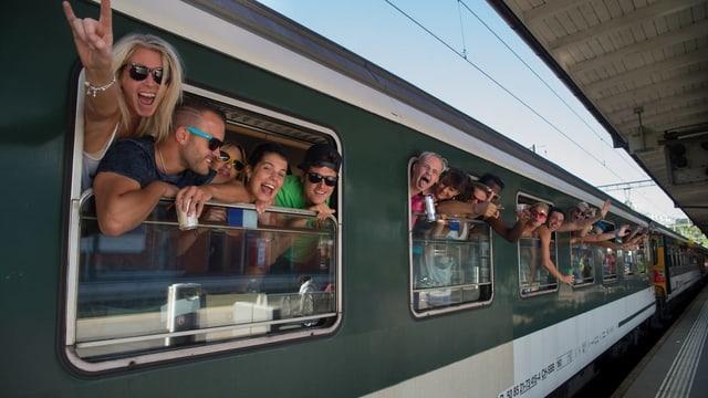 Tren special cun viagiaturs giuvens che guardan ord fanestra.