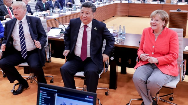 Donald Trump (links), Xi Jinping (Mitte) und Angela Merkel (rechts) sitzen nebeneinander