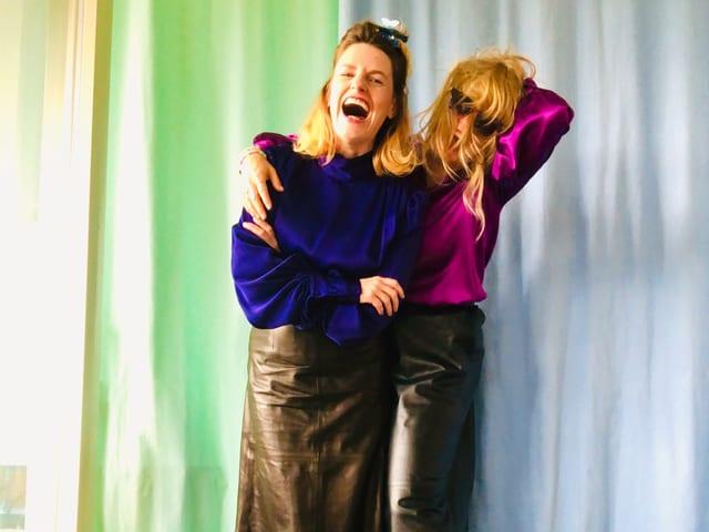 Zwei Frauen in bunter Kleidung vor einem blauen und einem grünen Aushang