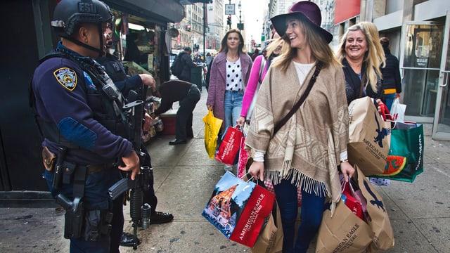 Zwei Frauen bepackt mit Einkaufstaschen gehen auf die Kamera zu und blicken auf zwei Polizisten links im Bild