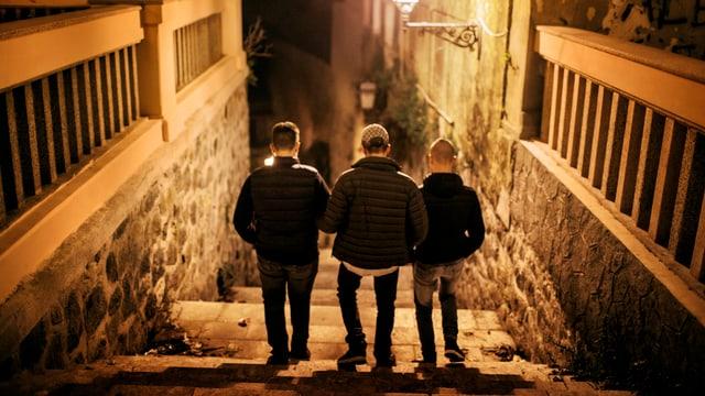 Drei Jungen gehen im Licht der Strassenlaterne eine Treppe hinunter.