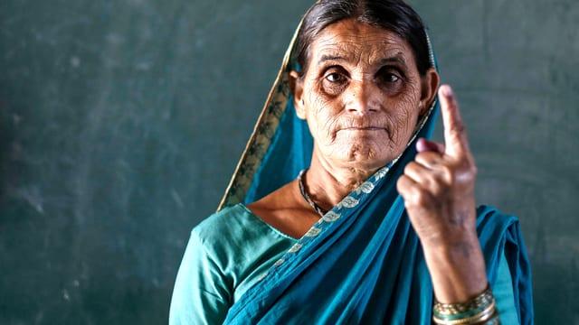 Frau in Indien hält den Finger hoch, der gefärbt ist.