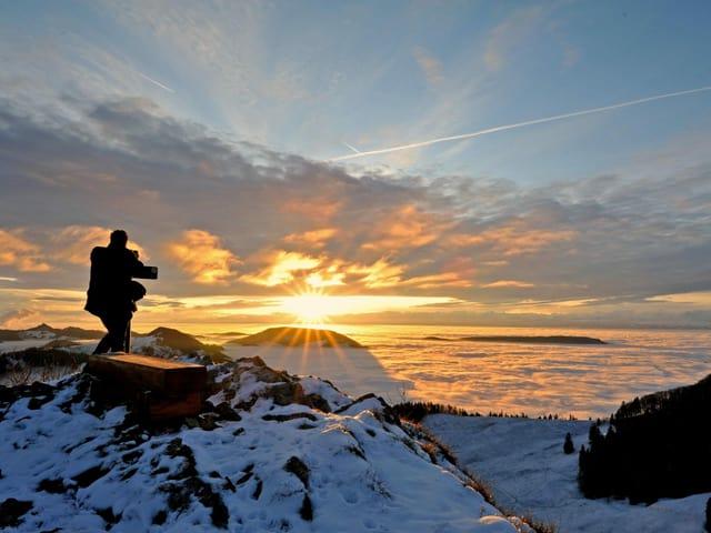 Sonnenaufgang in den verschneiten Bergen, ein Fotograf steht am Gipfel.