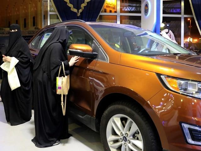 Frau schaut in Auto hinein.