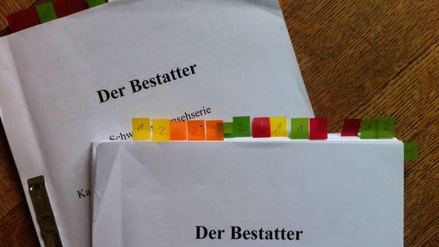 Zwei Drehbücher mit farbigen Post-Its, die gewisse Seiten mit farben markieren.