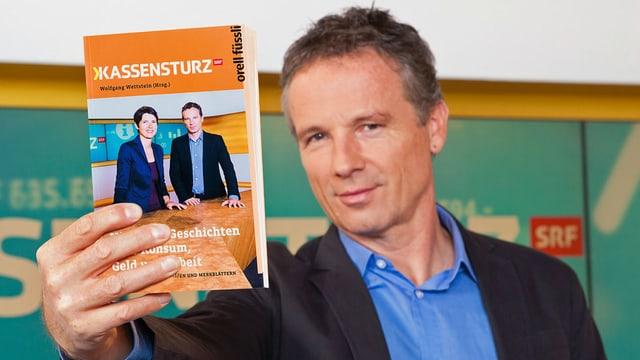 Kassensturz-Moderator Ueli Schmezer präsentiert im Studio das neue Kassensturz-Buch.