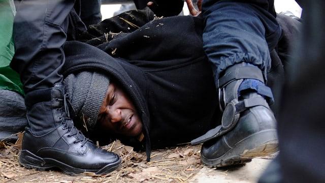Afroamerikaner wird von Polizisten auf den Boden gedrückt, ihm werden Handschellen angelegt.