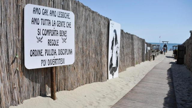 Ein Plakat am Strandweg zeigt die Aufschrift: Ich liebe Schwule, Lesben und alle, die sich gut benehmen. Regel: Ordnung, Sauberkeit, Disziplin und dann das Vergnügen.