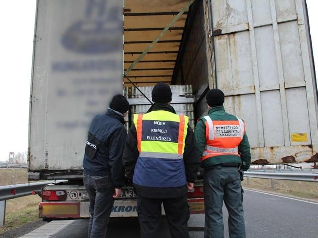 Polizisten schauen in den Laderaum eines Lastwagens.