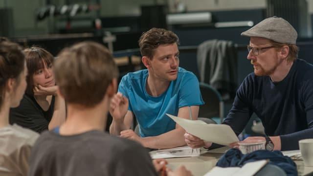 Regisseur Daniel Kuschewski in Diskussion mit Leuten seines Theaterprojekts.