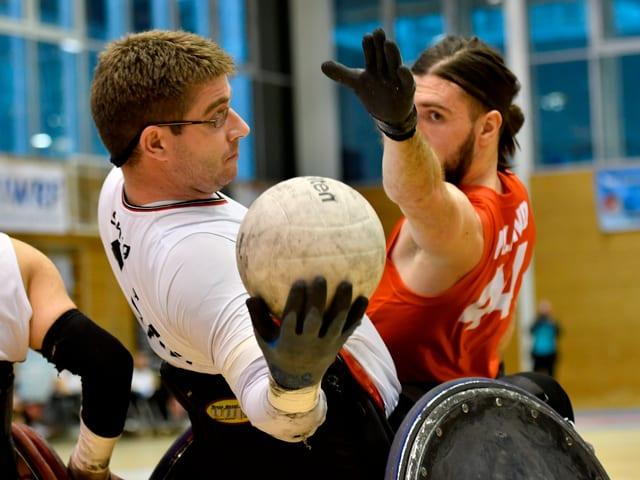 Zwei Männer spielen Rollstuhl-Rugby und kämpfen um den Spielball.
