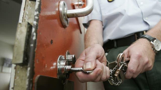 Ein Gefängnisaufseher schliesst eine Zelle auf.