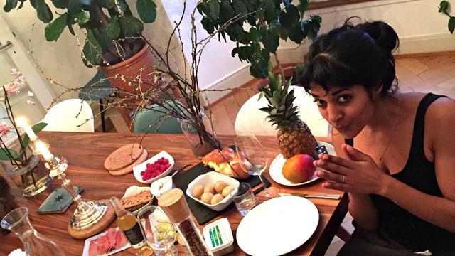 Reena sitzt am vollen Tisch und reibt sich die Hände