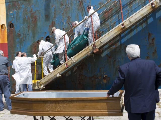 Männer in weisser Schutzbekleidung tragen eine Leiche in einem grünen Sack eine Schiffsleiter hinab. Unten wartet der Bestatter mit dem offenen Sarg.