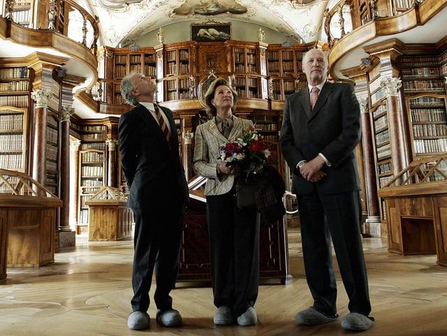 Drei Personen in der Stiftsbibliothek stehend.