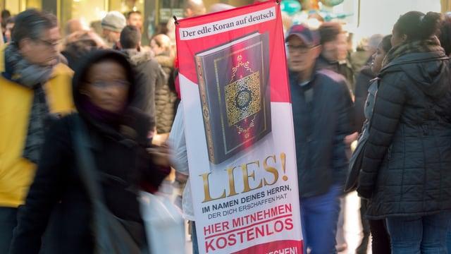 """Ein Banner der Aktion """"Lies!"""" mit dem Koran, verschwommene Passanten."""