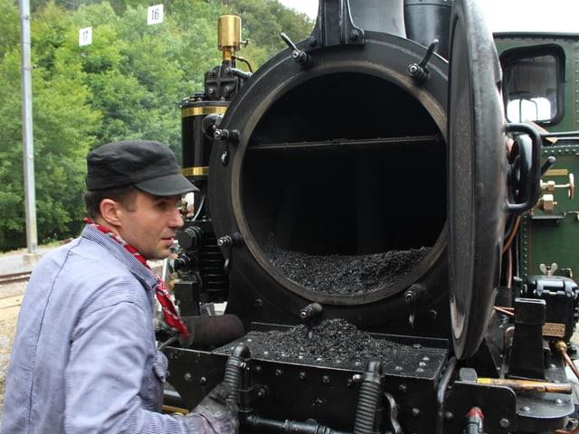 Der Heizer steht an der Nase der Dampflock vor der geöffneten Rauchkammertür.