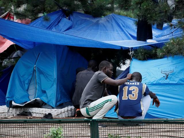 blaue Campingzelte mit Menschen, die davor sitzen
