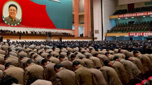 Staatsangestellte und Armeeangehörige verneigen sich in einem grossen Saal, an der Wand hängt ein Portrait von Kim Jong Il.