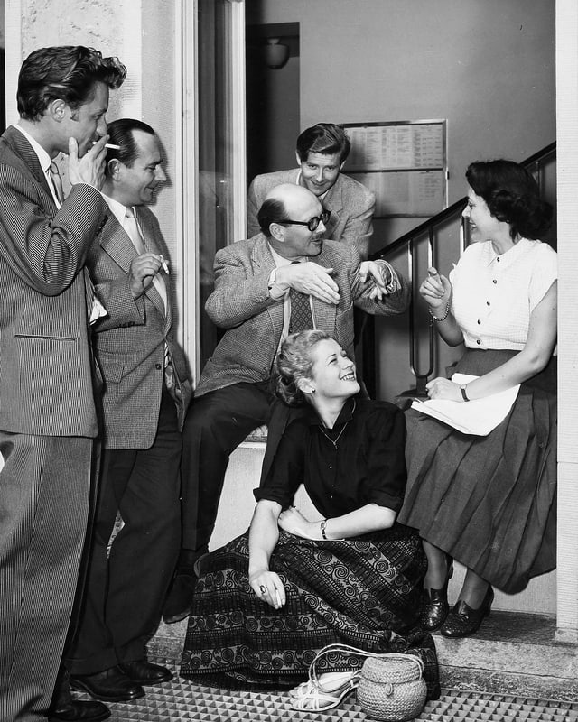 Zwei Frauen und vier Männer, die im Treppenhaus rege diskutieren.