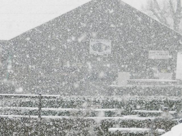 Wegen starkem Schnee ist ein Holzhaus kaum mehr zu sehen.