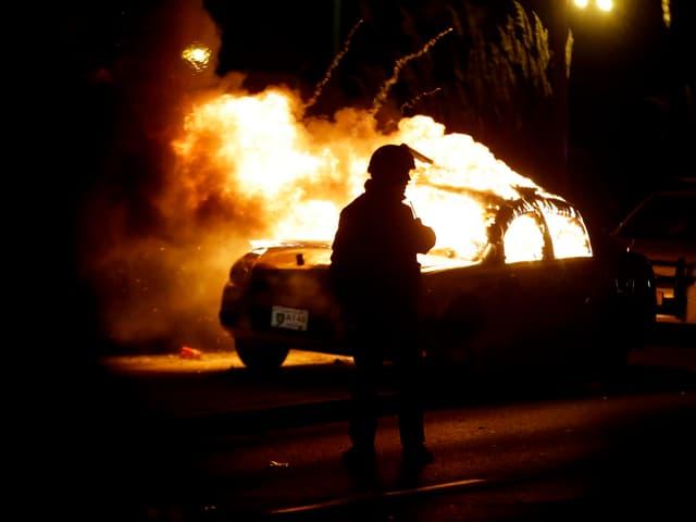 Feuerwehrmann steht vor brenndem Polizeiwagen