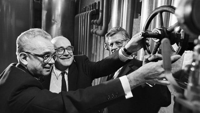 Drei Männer drehen an einem Rad in einem Keller voller Leitungen, Schwarz/Weiss-Bild