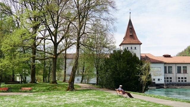 Im Hintergrund ein Gebäude, im Vordergurn sitzt ein Mann auf einer Bank auf einer grünen Wiese
