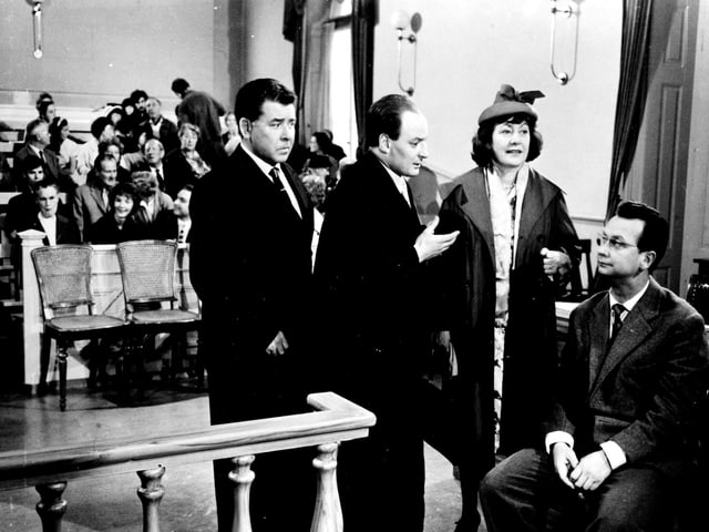 Drei Männer und eine Frau diskutieren in einem Gerichtssaal. Im Hintergrund sitzen Menschen und verfolgen die Diskussion.