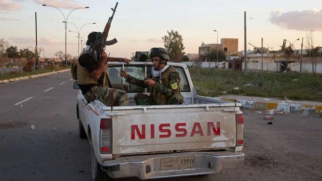 Schiitische Milizen auf einem Nissan-Truck patrouillieren durch die leeren Strassen von Tikrit.