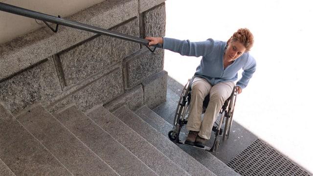 Eine Frau im Rollstohl am Fuss einer Treppe