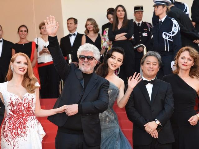 Almodovar auf dem roten Teppich zusammen mit den anderen Jurymitgliedern. Er winkt und trägt eine Sonnenbrille.
