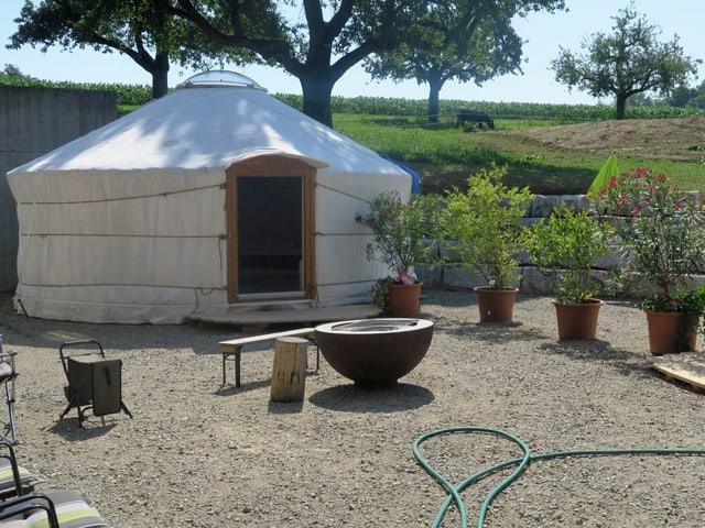 Ein weisses Zelt steht auf einem Kiesplatz.