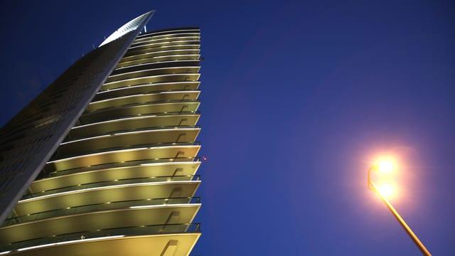 Ein 26-stöckiger Turm ragt in den Himmel, rechts im Bild eine brennende Laterne.