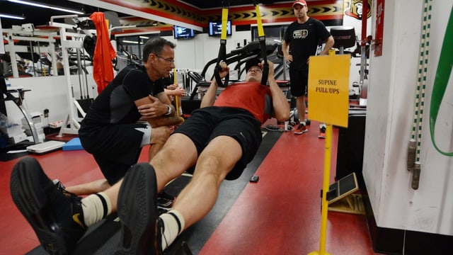 Ein Sportler beim Krafttraining mit einer Maschine in einer Sporthalle.