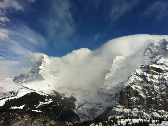 Blick auf die Jungfrauregion. Von der einen Seite drückt eine Wolkenwand heran, auf der anderen Seite stürzt die Luft ins Tal, die Wolke löst sich auf.