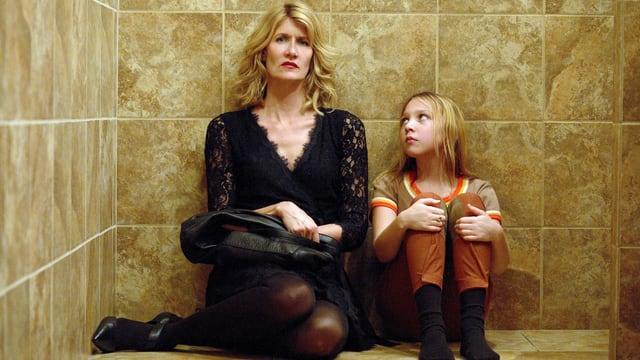 Eine erwachsene Frau und ein Mädchen sitzen auf dem gekachelten Boden.