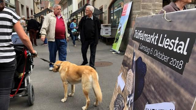 Ein Schild mit der Aufschrift «Trüffelmarkt Liestal», mehrere Menschen und ein Hund.