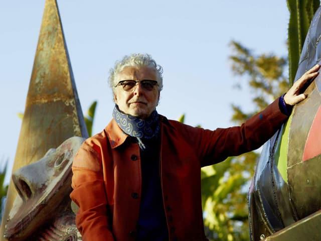 Ein Mann in einem garten streichelt einen Dinosaurier.