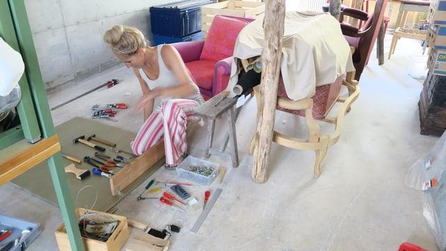 Eine Frau in einem Atelier kauert am Boden, vor sich diverse Werkzeuge.