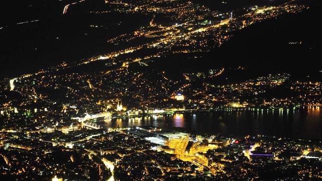 Blick auf das nächtliche Luzern. Einzelne Zentren sind hell beleuchtet, andere dunkel.