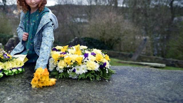 Ein Kind legt Blumen auf einen grossen Stein auf dem Friedhof.