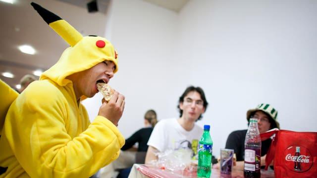 Ein junger Mann im Pikachu-Kostüm beisst in einen Hamburger.