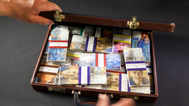 Ein Koffer gefüllt mit Schweizer Banknoten ist zu sehen.
